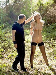 Tormenting blonde teen slave in the woods